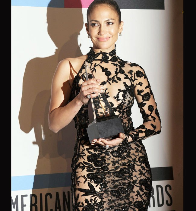Singer Jennifer Lopez poses backstage after winning the Favorite Latin Music Artist award at the 2011 American Music Awards in Los Angeles