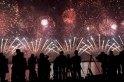 Journalists watch a fireworks display to