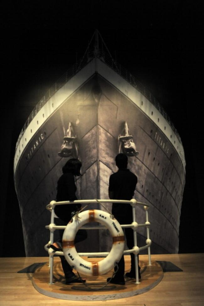 Two visitors stand in front a poster of the sunken ship Titanic