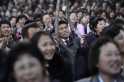 North Koreans sing as they wait for a fi