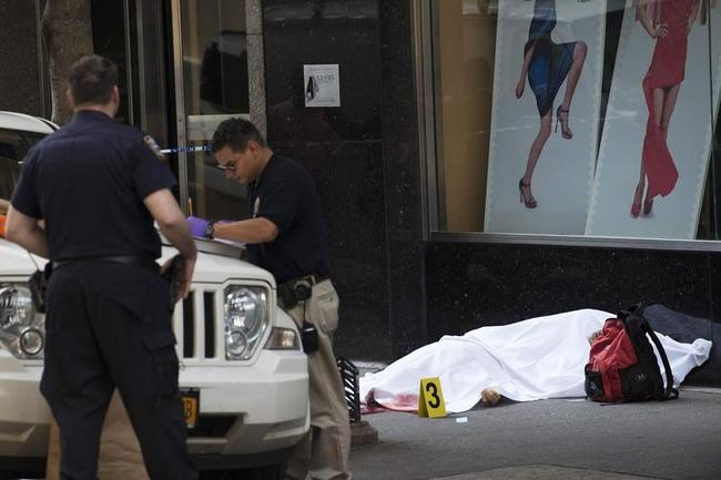 New York City Police detectives examine the scene next to the body of a suspected shooter that opened fire shooting several bystanders near the Empire State Building