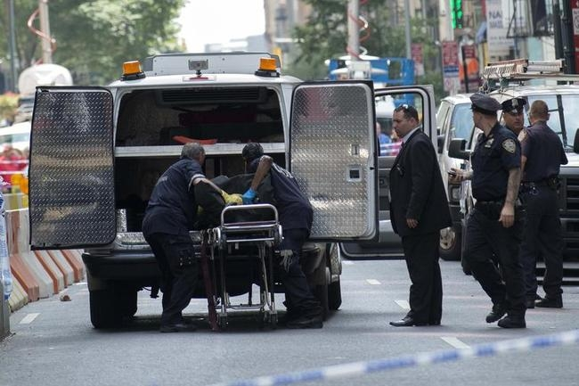 The body of a shooting victim is moved by the New York City Coroner near the site of the Empire State building where a gunman opened fire shooting several bystanders before being killed by police in New York