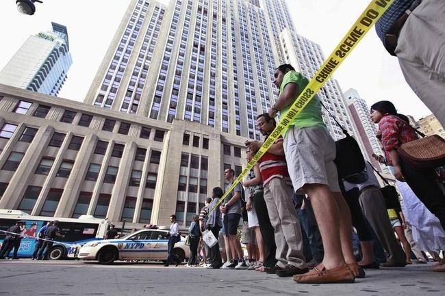 People stand near a police line at the scene of a shooting outside the Empire State Building in New York