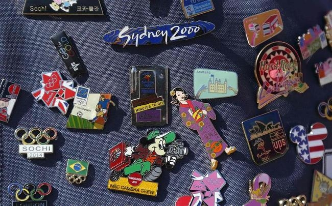 Pins collected by Linda Li of Guangzhou, China are displayed on her purse outside Olympic Village in east London