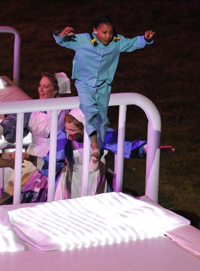 A child performs on a trampoline as danc