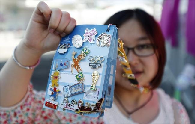 Pin collector Linda Li of Guangzhou, China holds some of her pins outside the Olympic Village in Stratford in east London