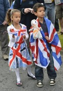 Spectators watch as a torchbearer runs in the Olympic Torch Relay in Plymouth, south west England