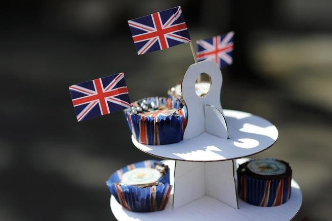 Cakes are displayed on a cake stand during a street party
