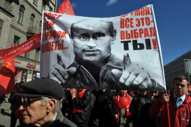 Russian communist party supporters hold a poster of Vladimir Putin picture reading
