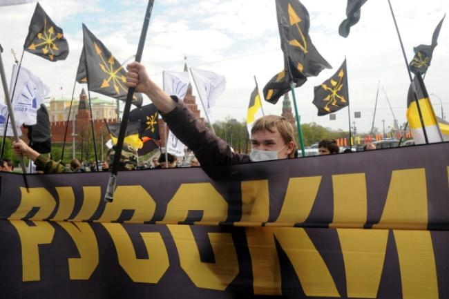 Russian nationalist supporters carry flags and a poster reading