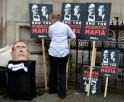 A mask (L) depicting James Murdoch, son of media mogul Rupert Murdoch