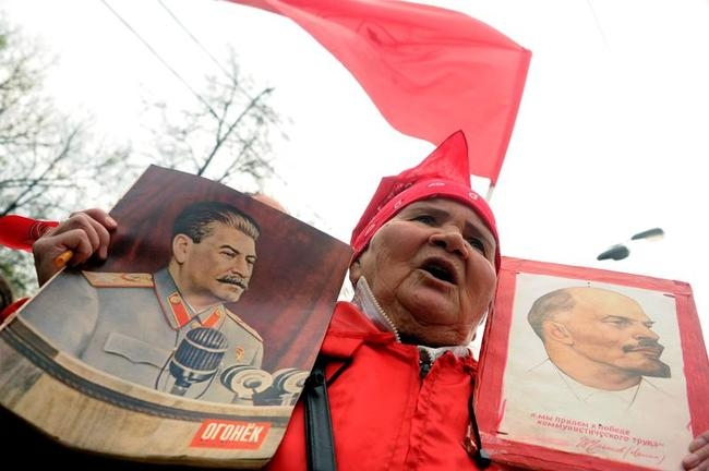 Russian communist pary supporter holds pictures of Josef Stalin (L) and Vladimir Lenin (R)