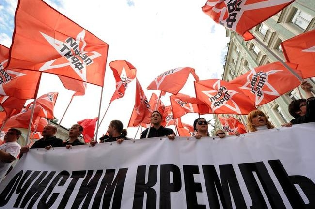 Russian communist pary supporters carry red flags and a poster reading