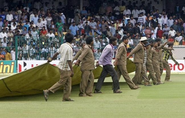 Groundsmen bring out a rain cover onto the field during the fourth day of the second test cricket match between India and New Zealand in Bangalore