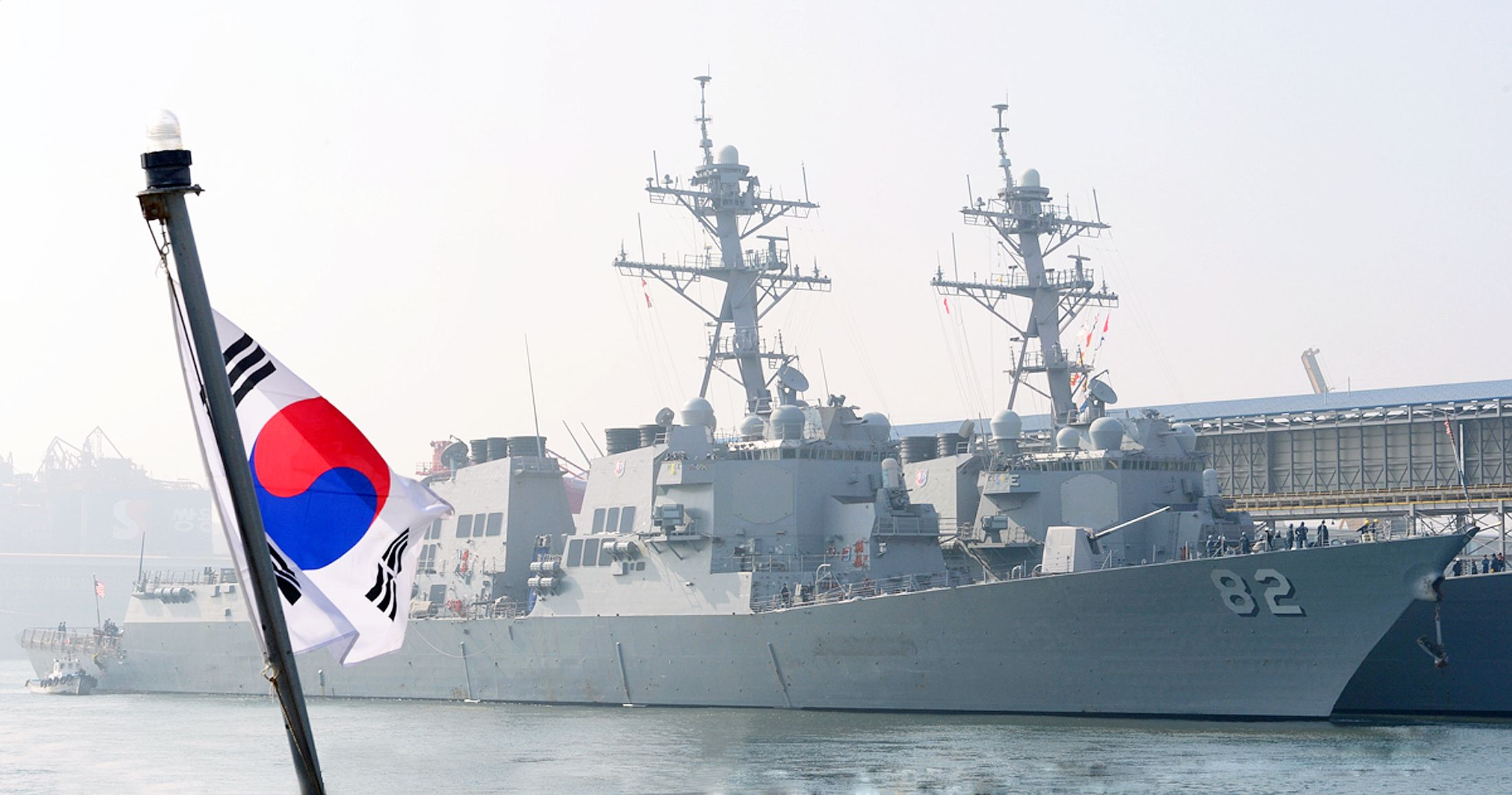 South Korean navy sailors wave South Korean and U.S. national flags at a naval port in Donghae