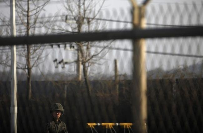 A South Korean soldier stands guard near a barbed wire fence at a checkpoint on the Grand Unification Bridge, which leads to the demilitarized zone separating North Korea from South Korea, in Paju