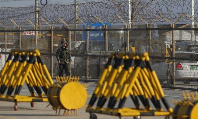 A South Korean soldier walks along a barbed wire fence at a checkpoint on the Grand Unification Bridge, which leads to the demilitarized zone separating North Korea from South Korea, in Paju