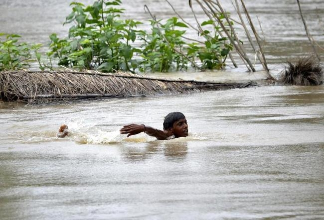 A flood-affected villager swims through the flooded waters of river Ganges after heavy rains at Patna district