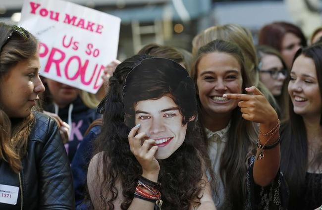 "A fan holds a mask depicting One Direction band member Harry Styles, as she waits for the premier of the film ""One Direction: This is Us"", in London"
