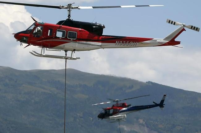 Helicopters fill buckets of water to fight the Rockport Fire near Rockport State Park in Utah