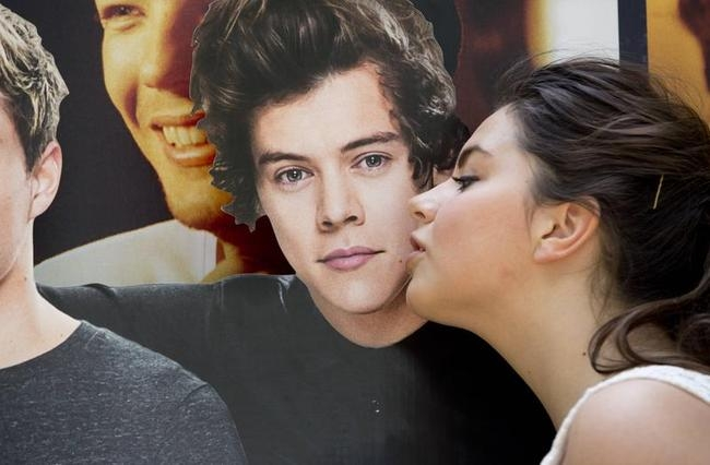 "A One Direction fan kisses a life-size cutout of Harry Styles as she waits for the premiere of the film ""One Direction: This is Us"", in London"