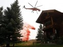 A helicopter tanker drops fire retardant near a home at the Beaver Creek wildfire outside Ketchum