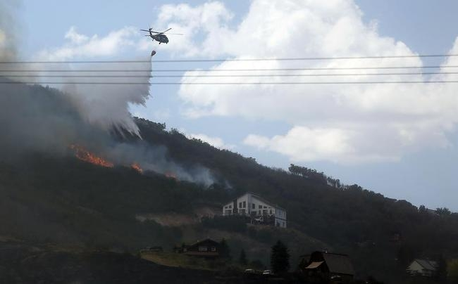 Helicopter drops water on a fire that flared up near a home at the Rockport Fire near Rockport State Park in Utah