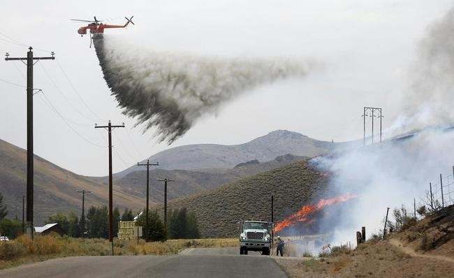 A tanker helicopter drops water as a firefighter works to douse a hot spot at the Beaver Creek wildfire outside Hailey, Idaho