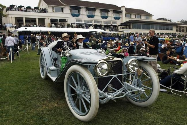 A 1914 American Underslung 642 Roadster drives off the stage during the Concours d