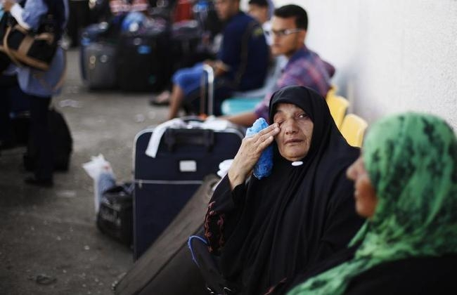 Palestinians wait to cross into Egypt at Rafah crossing, between Egypt and southern Gaza Strip
