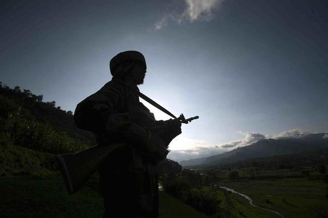 An Indian army soldier stands guard while patrolling near the Line of Control, a ceasefire line dividing Kashmir between India and Pakistan, in Poonch