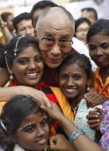 Exiled Tibetan spiritual leader the Dalai Lama poses for a picture along with street children adopted by a charitable day-boarding school in New Delhi