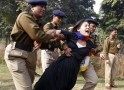 A Tibetan exile is detained by police during a protest over China