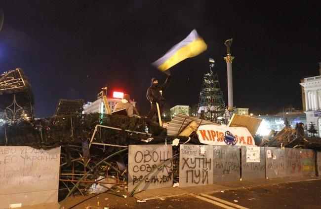 A protester waving the national flag stands on a barricade at Independence Square in Kiev