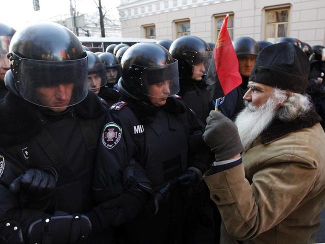 A protestor holds a flag as he stands in front of a police line during a demonstration in support of EU integration in Kiev