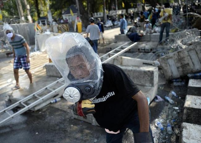 An anti-government protester uses personalised protective gear as they attempt to remove barricades outside Government House in Bangkok