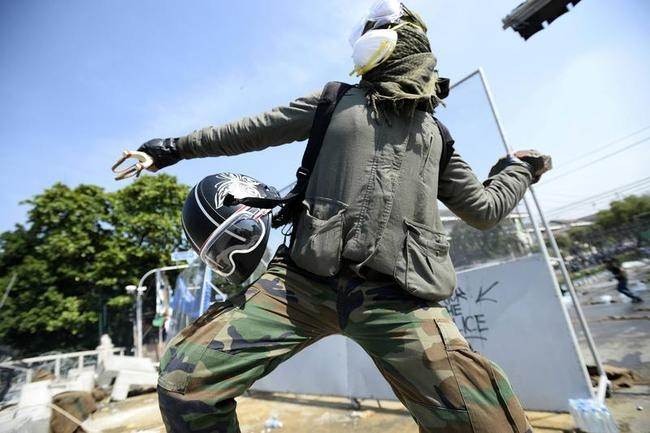 An anti-government protester throws a rock at Thai riot police as they attempt to remove barricades outside Government House in Bangkok