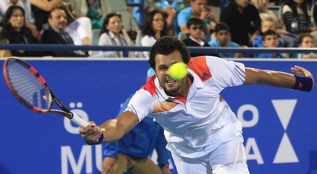 Jo-Wilfried Tsonga hits a return to Novak Djokovic during their semi-final tennis match at the Mubadala World Tennis Championship in Abu Dhabi