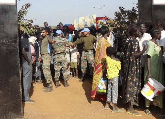 Handout photo of a contingent of peacekeepers from UNMISS guiding civilians arriving at the UN compound in the outskirts of Juba