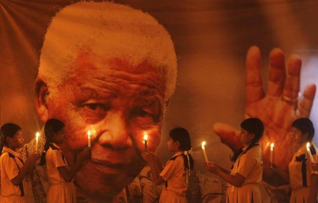 Schoolgirls hold candles in front of poster of former South African President Mandela during prayer ceremony at school in Chennai