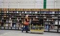 Worker transports items for delivery from warehouse floor at Amazon