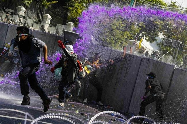 Anti-government protesters flee as riot policemen use water cannon during clashes with the police the metropolitan police headquarters in Bangkok