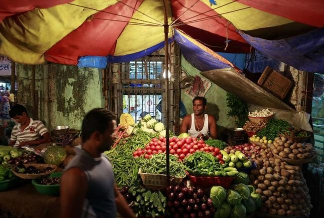 Vendor selling vegetables waits for customers at his stall at a market in Mumbai