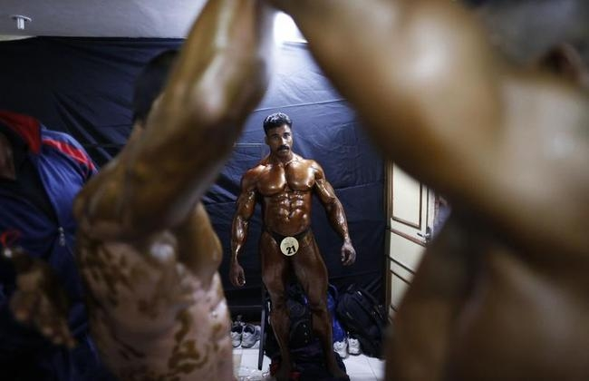 Competitors have tanning lotion applied on their bodies during a bodybuilding competition in Mumbai