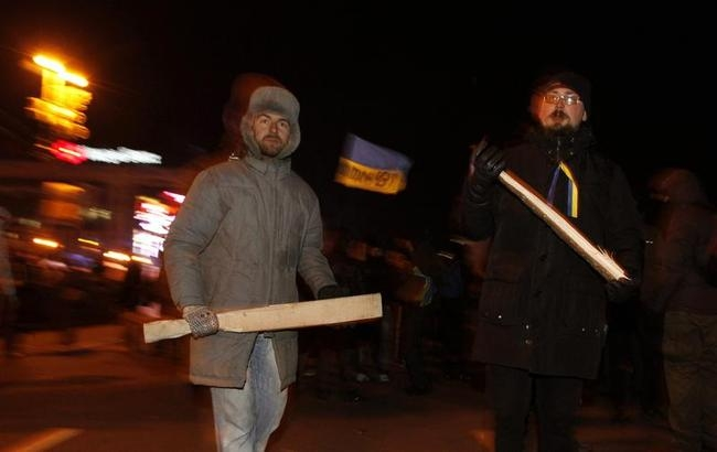 Protesters with wooden sticks walk at a barricade at Independence Square in Kiev