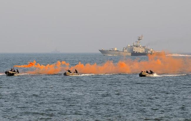 Indian Navy personnel dispense smoke from canisters during a dress rehearsal ahead of Navy Day celebrations in Visakhapatnam