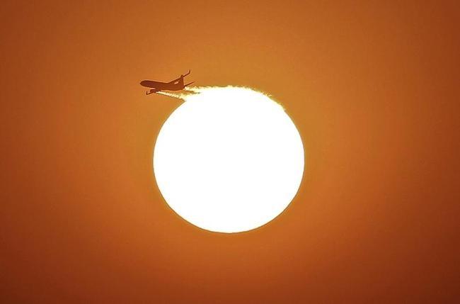 An aircraft files near the setting sun in New Delhi