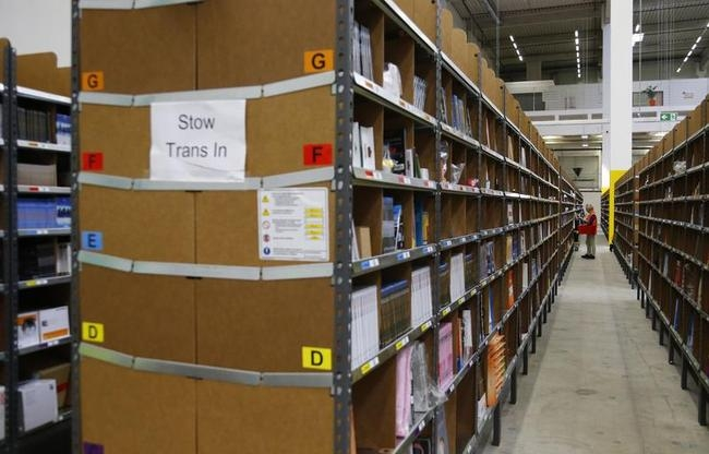 Worker sorts items for delivery from warehouse floor at Amazon