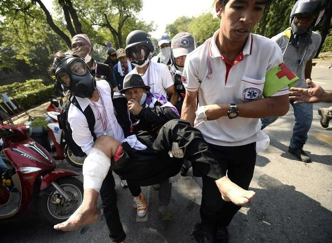 An anti-government protester, who was hit with a rubber bullet fired by Thai riot police, is carried by medical staff outside Government House in Bangkok