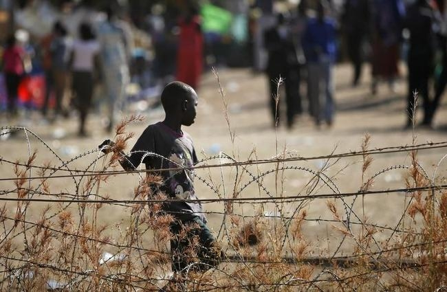 An internally displaced boy walks next to barbed wire inside a UNMIS compound in Juba